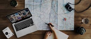Travel planning with a map, camera, laptop and notebook