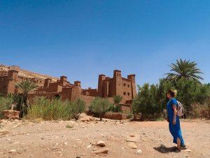 Walking to the Kasbah of Ait Banhaddou wearing a blue traditional Berber dress in Morocco