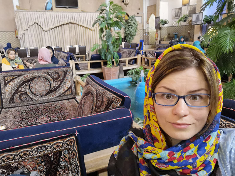 Selfie in a traditinal Persian restauran. The furniture used for eating is called takht sonati. It's a kind of wooden bed covered with solorful Persian carpet and cushions.