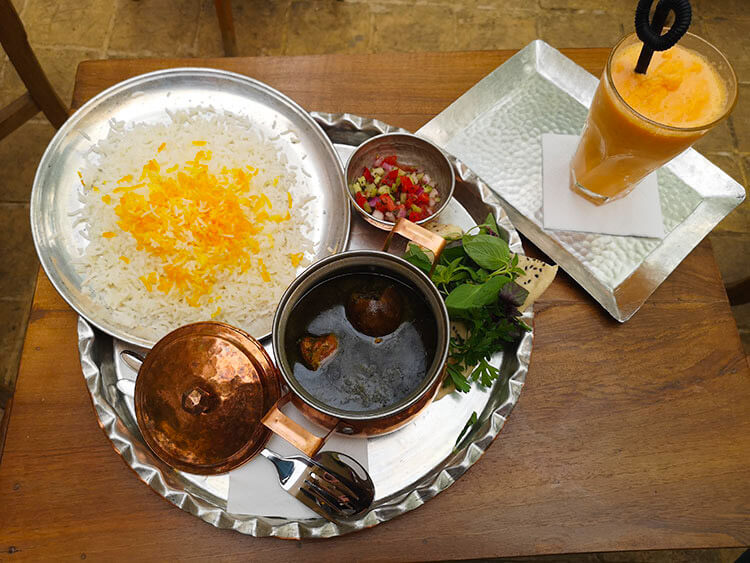 Traditional Persian food Ghormeh Sabzi, rice with saffran, Persian bread, herbs and salad served with saffran juice