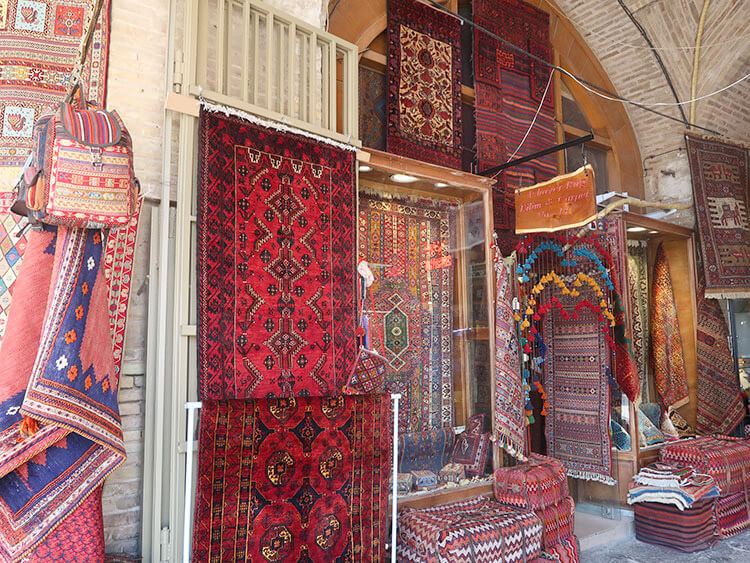 Colorful Persian carpets are hanging outside in front a carper shop in the Grand Bazaar of Isfahan, Iran