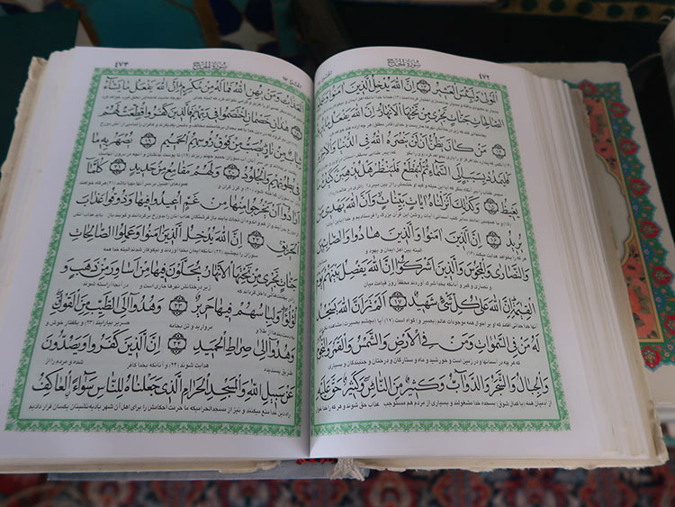 Quran open on a table. the text is in Arabic with Persian translation